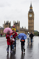 © Licensed to London News Pictures. 14/05/2015. London, UK. A family with umbrellas cross Westminster Bridge in front of Big Ben during heavy rain and wet and windy weather in Westminster, central London today. Photo credit : Vickie Flores/LNP