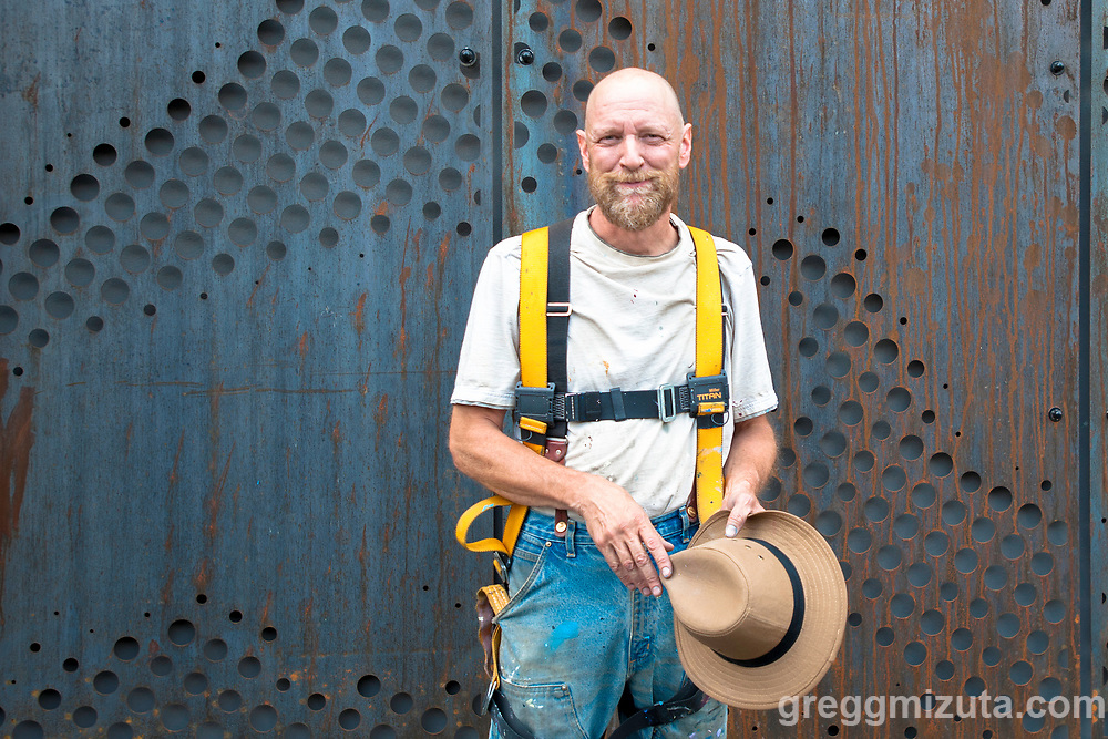Portland, Oregon-based artist David Carmack Lewis takes a break from painting his mural on west side of The Fowler in Boise, Idaho on August 11, 2018.<br /> <br /> Lewis started the mural on July 21 and finished it on August 15th. The mural covers approximately 40 percent of the building closest to Myrtle Street, and works its exterior features like windows into a stylized depiction of the Boise Foothills against a partly cloudy sky.