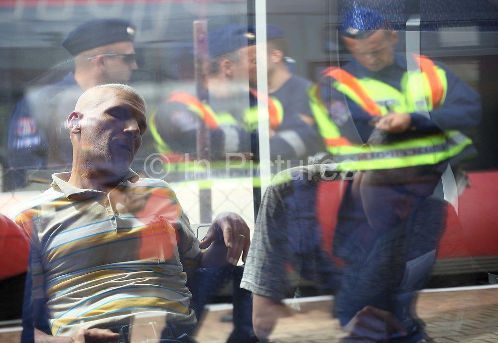 A man sleeps on a train carrying migrants from Budapest to Vienna at  train station in Hegyeshalom on the border of Hungary and Austria, September 6 2015. Hundreds of migrants have resumed their journey through Austria to Germany after Hungary's decision on Friday to let them through.