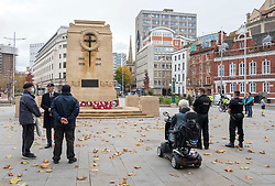 © Licensed to London News Pictures; 11/11/2020; Bristol, UK. People wait for 11am on Remembrance Day at the Bristol Cenotaph in the city centre. The normal large military parade and civic procession was cancelled due to the national lockdown restrictions for the Covid-19 coronavirus pandemic, but around 40 people gathered for the two-minute silence that traditionally takes place at 11.00am, recognising the precise time that the hostilities ceased in 1918 – the 11th hour of the 11th day of the 11th month. Photo credit: Simon Chapman/LNP.