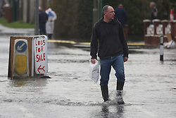 © Licensed to London News Pictures. 01/08/2014. Man in wellies at the flooded road by Chertsey Bridge on the Thames. Recent bad weather has caused the river Thames in south west London and Surrey to reach very high levels. Credit : Rob Powell/LNP