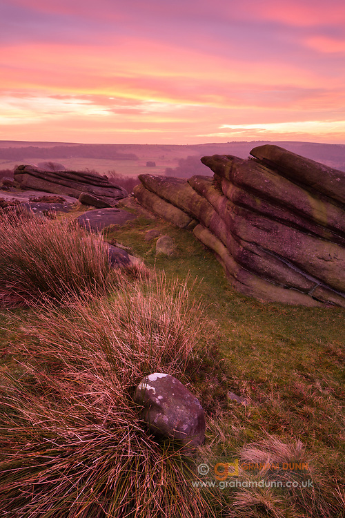 Incredible pre-dawn light reflects off the overhead clouds and lifts the foreground grasses and rocks in this landscape scene below Over Owler Tor in the Peak District. Hathersage Moor, Derbyshire, England, UK. Autumn, December.