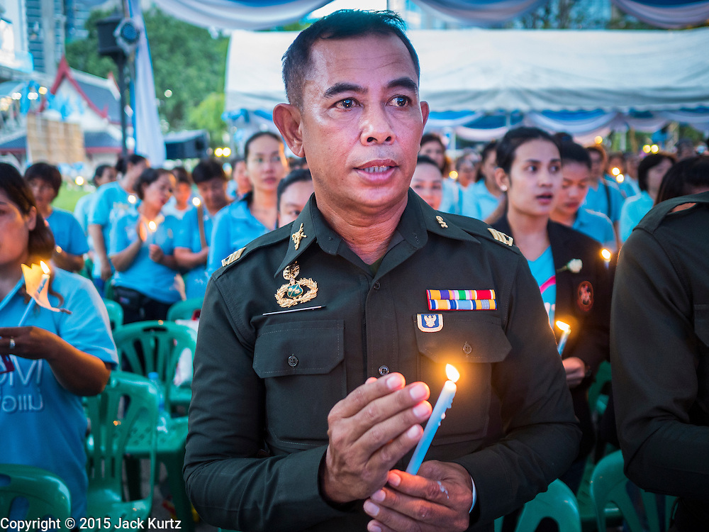 12 AUGUST 2015 - BANGKOK, THAILAND: A Thai police officer lights a candle for Queen Sirikit of Thailand on her 83rd birthday. Queen Sirikit was born Mom Rajawongse Sirikit Kitiyakara on August 12, 1932. She is the queen consort of Bhumibol Adulyadej, King (Rama IX) of Thailand. She met Bhumibol in Paris, where her father was the Thai ambassador. They married in 1950, she was appointed Queen Regent in 1956. The King and Queen had one son and three daughters. She has not made any public appearances since her hospitalization in 2012. Her birthday is celebrated as Mother's Day in Thailand, schools and temples across Thailand hold ceremonies to honor the Queen and mothers.     PHOTO BY JACK KURTZ