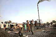 Young workers are feeding a series of large boilers in an illegal dumping and burning ground located on the banks of the holy Ganges River near the tannery area of Jajmau, Kanpur, Uttar Pradesh, India. The scrap leather is destined to be boiled and reduced to a thin dust: the raw material for fertilisers and chicken food production.