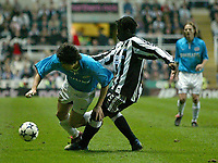 Photo. Andrew Unwin.<br /> Newcastle United v PSV Eindhoven, UEFA Cup Quarter Final Second Leg, St James' Park, Newcastle upon Tyne 14/04/2004.<br /> PSV's Ji-Sung Park (l) is tackled by Newcastle's Olivier Bernard (r).
