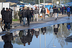 © Licensed to London News Pictures. 23/10/2016. Calais, France. Migrants walk past surface water. Daily life continues as preparations begin for the demolition of the migrant camp in Calais, France, known as the 'Jungle'. French authorities have given an eviction order to thousands of refugees and migrants living at the makeshift living area of the French coast. Photo credit: Ben Cawthra/LNP