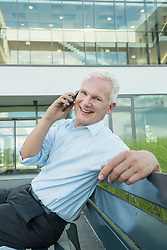 portrait of businessman sitting on a bench using his smartphone
