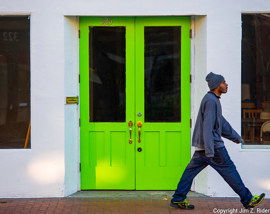 A man passes a vibrant green doorway in downtown Portland, Oregon.
