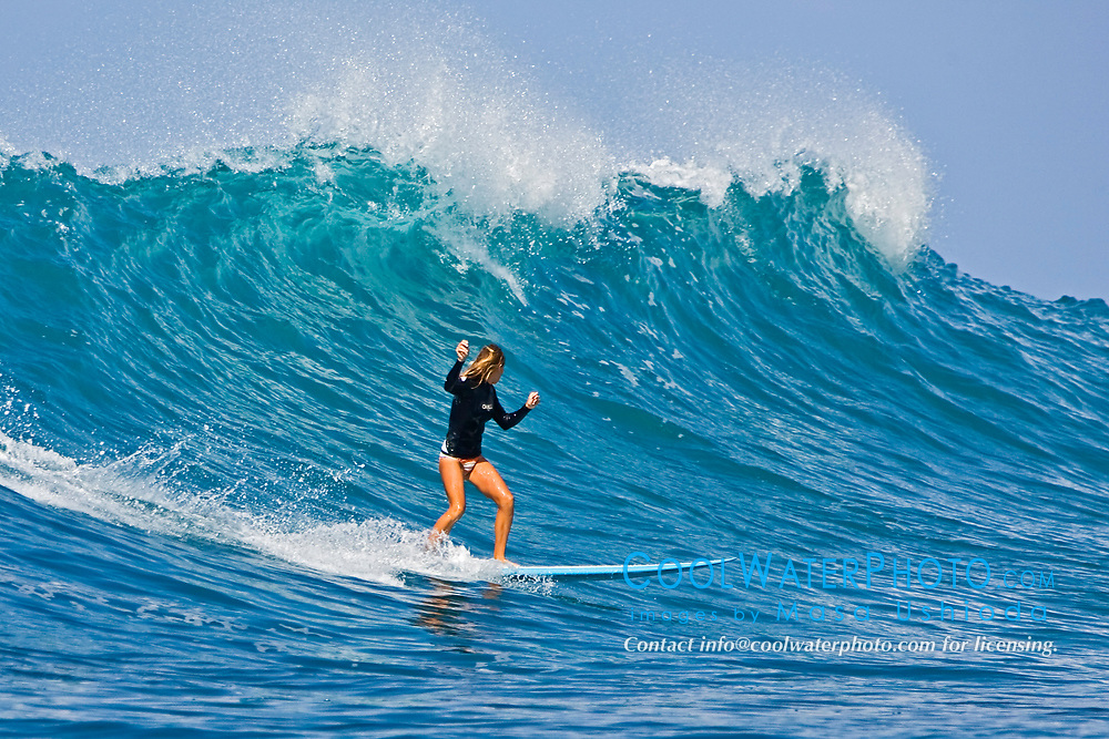 Woman surfer, riding a rare big ocean wave in Kona Coast, Keauhou Bay, Big Island, Hawaii, Pacific Ocean