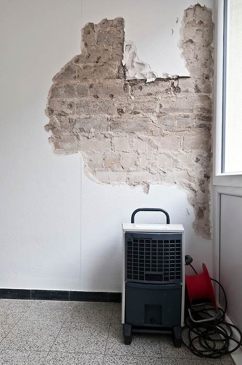 Wasserschaden in einem Wohnhaus wird mit Hilfe eines Trockengerätes zum Entziehen der Feuchtigkeit aus der Wand behoben,       