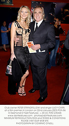 Club owner PETER STRINGFELLOW and singer LUCY CARR, at a film premier in London on 22nd January 2003.PGN 86