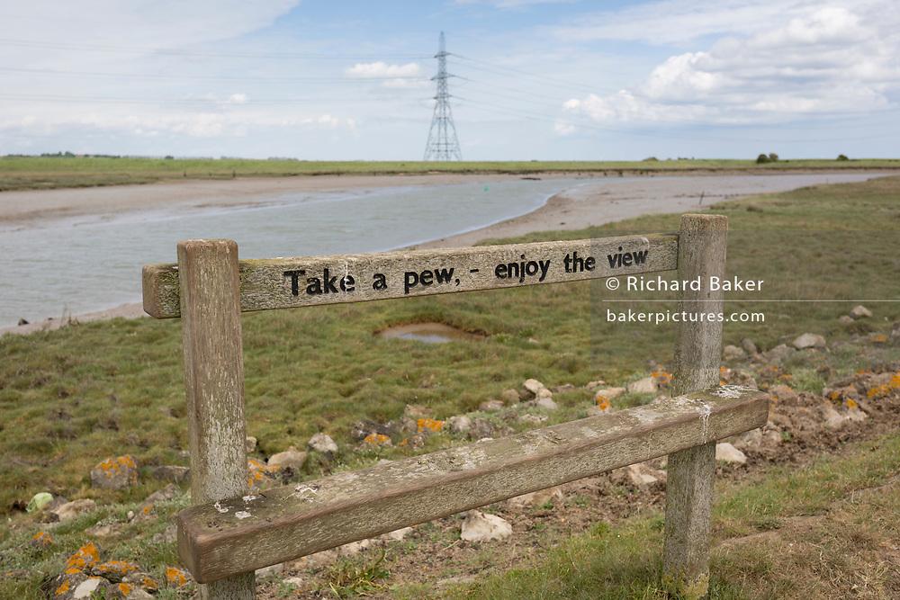 A rest bench and pylon landscape on the Saxon Shore Way on Faversham Creek near Hollowshore, on 29th May 2019, near Faversham, Kent, England.