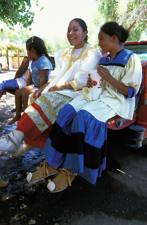 Apache girls dressed in camp dresses and moccasins sit on the platform of a pickup truck during a Sun Rise Dance, a first menstruation rite, on the San Carlos Apache Indian Reservation in Arizona, USA.
