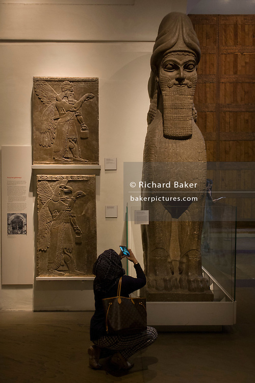 Muslim visitor takes a photo with a smartphone of  a giant Assyrian Winged human-headed lion from about 865-860BC from the ancient city of Numrud. This protective spirit guarded the entrance into what may have been a banquet hall.