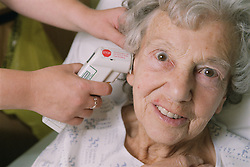 Elderly female patient having temperature checked using a Tympanic thermometer,