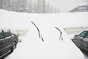 A parked car lies covered in snow, with only windshield wipers visible, at Snoqualmie Pass, Washington, on February 2, 2008. The pass was closed soon after due to the unusually heavy snowfall.