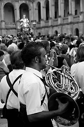 Lecce - Festeggiamenti in onore di Sant'Oronzo, San Giusto e San Fortunato. In primo piano i componenti della banda intonano le note per accogliere il passaggio della statua del santo che si vede sullo sfondo.