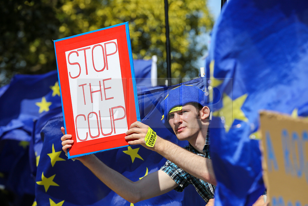 """© Licensed to London News Pictures. 04/009/2019. London, UK. """"Stop the Coup"""" protester holds a placard demonstrates outside Parliament. On Monday 3 Sept 2019, MP's voted by 328 -301 with a majority of 27 to take control of the House of Commons agenda for Tuesday 4 Sept 2019. Photo credit: Dinendra Haria/LNP"""