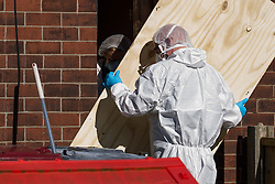 © Licensed to London News Pictures . 10/03/2014 . Farnworth , UK . Forensic examiners unscrew a plywood cover placed over the front door . Police and forensic scenes of crime examiners at a house on Kildare Street , Farnworth , where the body of 40 year old Marc Jepson was discovered on 5th March , as Greater Manchester Police announce that they have arrested two people as part of their murder enquiry . A 27 year old man and a 63 year old woman are in police custody for questioning . Photo credit : Joel Goodman/LNP