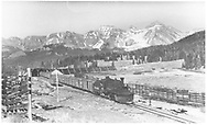 Leased D&RGW #464 with freight southbound out of snowshed on Lizard Head Pass.  Pyramid Peak and Yellow Mountain on skyline.<br /> RGS  Lizard Head, CO  Taken by Perry, Otto C. - 6/26/1945<br /> Also at RD137-141.
