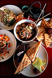 The Atomic Age Cafe & Lounge in Ybor City, features an eclectic menu. From bottum clockwise: Grilled Vegetable Dagwood sandwich, Korean Calamari Stir Fry, Chopped Vegetable salad, Honey Ginseng Tea, Black Bean Hummus with grilled flat bread, and  Hot & Sour Shrimp with rice noodles and Thai herbs (center). (Photo © Jock Fistick)
