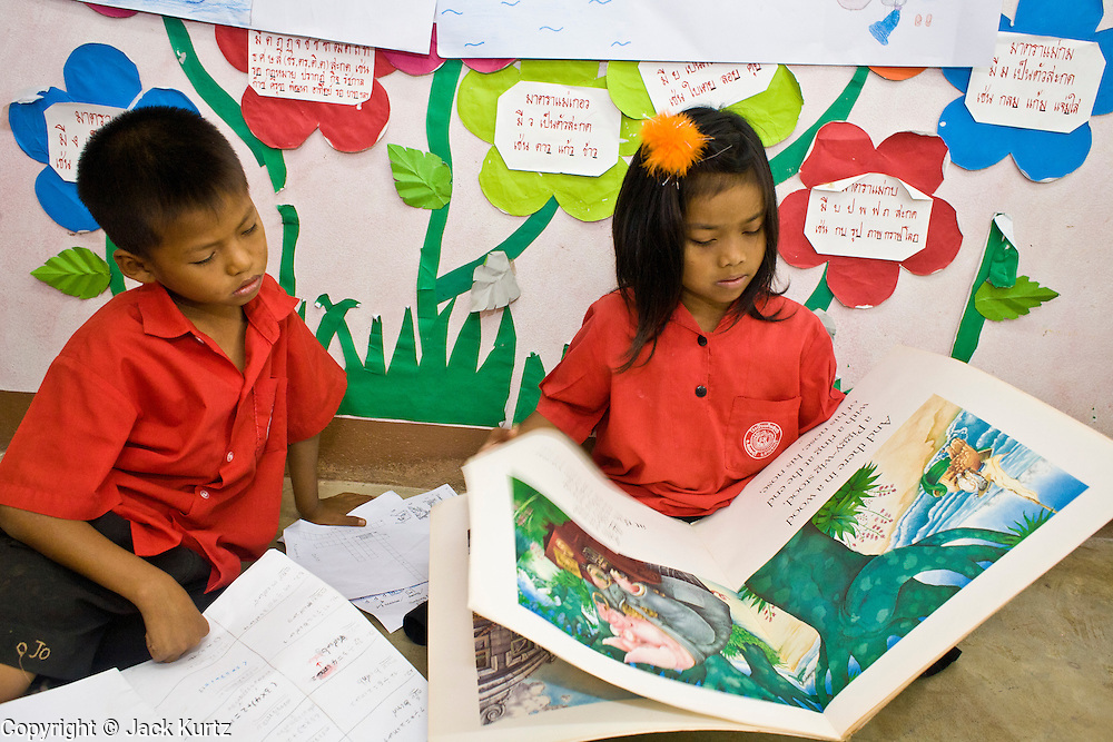 """19 FEBRUARY 2008 -- SANGKLABURI, KANCHANABURI, THAILAND: Second grade Burmese refugee students study English at Baan Unrak School in Sangklaburi, Thailand. The school's curriculum is in taught in Thai but the children start studying English in second grade. Baan Unrak children's home and school, established in 1991 in Sangklaburi, Thailand, gives destitute children and mothers a home and career training for a better future. Baan Unrak, the """"Home of Joy,"""" provides basic needs to well over 100 children, and  abandoned mothers. The home is funded by donations and the proceeds from the weaving and sewing shops at the home. The home is a few kilometers from the Burmese border. All of the women and children at the home are refugees from political violence and extreme poverty in Burma, most are Karen hill tribe people, the others are Mon hill tribe people. The home was started in 1991 when Didi Devamala went to Sangklaburi to start an agricultural project. An abandoned wife asked Devmala to help her take care of her child. Devmala took the child in and soon other Burmese women approached her looking for help.    Photo by Jack Kurtz"""