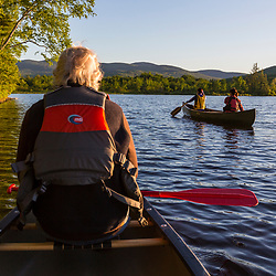 A man watches as two women paddle a canoe in the morning on Silver Lake in Piscataquis County, Maine. Near Greenville.