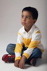 Young boy sitting cross legged on the floor,