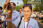 06 JANUARY 2013 - BANGKOK, THAILAND: A woman rings a prayer bell during a service honoring a relic of the Buddhas' hair. The relic has been on display in Bangkok for about 10 years. There was a ceremony in Sanam Luang in Bangkok Sunday to honor the relic. People prayed for it and received blessings from Buddhist monks and Brahmin priests who presided over the service. The hair is being moved to Ayutthaya, where it will be displayed in a Buddhist temple. The piece of hair has been on loan to Thai Buddhists from a Buddhist temple in Sri Lanka.    PHOTO BY JACK KURTZ