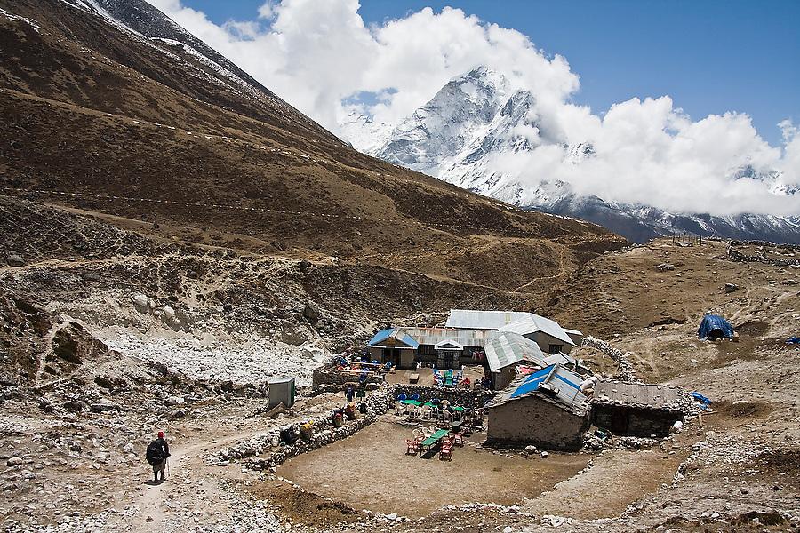 A trekking porter walks towards the lodges of Duglha and the towering peak of Ama Dablam, along the trail to Everest, Khumbu region, Sagarmatha National Park, Himalaya Mountains, Nepal.