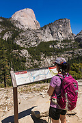 Hiker reading interpretive sign on the John Muir Trail under Half Dome, Yosemite National Park, California USA