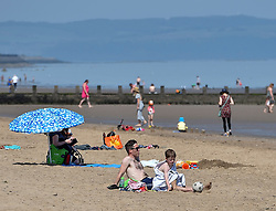 Portobello beach was busy on the first day of phase 1 of the reduction in Covid lockdown in Scotland. Police kept a low profile, leaving the sunbathers and swimmers to themselves.<br /> <br /> © Dave Johnston / EEm