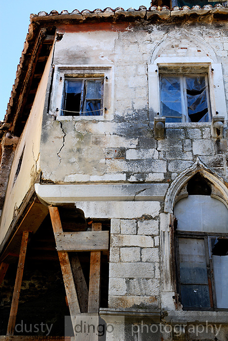 Section of building beginning to crumble and crack, timber bracing holding it up. Trogir, Croatia