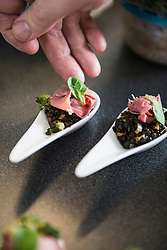Cook preparing appetizer made of black gram and ham on spoons