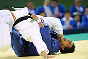 North Korea's PAK Chol Min (in white) fights Uzbekistan's Mirali SHARIPOV (in blue) during the less than 66 kg Men Judo competition. PAK won the match and the Olympics' Bronze medal