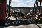 """Graffiti calling for """"Justice for Floyd"""" lines the charred remains of the Minnehaha Liquor store along Lake Street in Minneapolis, Minnesota on Monday, June 1, 2020."""