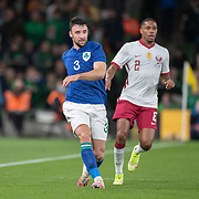 DUBLIN, IRELAND:  October 12:   Enda Stevens #3 of Republic of Ireland watched by Ró-Ró #2 of Qatar during the Republic of Ireland V Qatar International friendly match at Aviva Stadium on October 12th, 2021 in Dublin, Ireland. (Photo by Tim Clayton/Corbis via Getty Images)