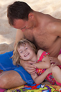 A little girl in her daddy's lap smiles happily on the beach