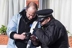 A forensics investigator and a police officer examine images on a camera at the scene of a 'small, contained' fire in Burnfoot Avenue, Fulham which claimed the life of a woman. Fulham, London. February 07 2018.