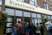 Broadway market. Hackney. Young saturday shoppers checking out the properties for sale at a local estate agent's, Blake Stanley.