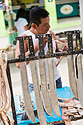 A villager views machete knives on sale at the Sunday market in Tlacolula de Matamoros, Mexico. The regional street market draws thousands of sellers and shoppers from throughout the Valles Centrales de Oaxaca.