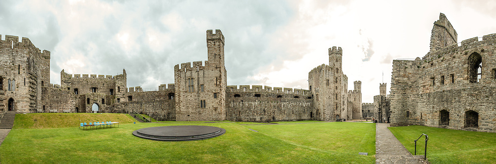 A panorama of the interior of Caernarfon Castle in northwest Wales. The slate dais in the center was used for the investiture ceremony of Prince Charles as Prince of Wales. A castle originally stood on the site dating back to the late 11th century, but in the late 13th century King Edward I commissioned a new structure that stands to this day. It has distinctive towers and is one of the best preserved of the series of castles Edward I commissioned.