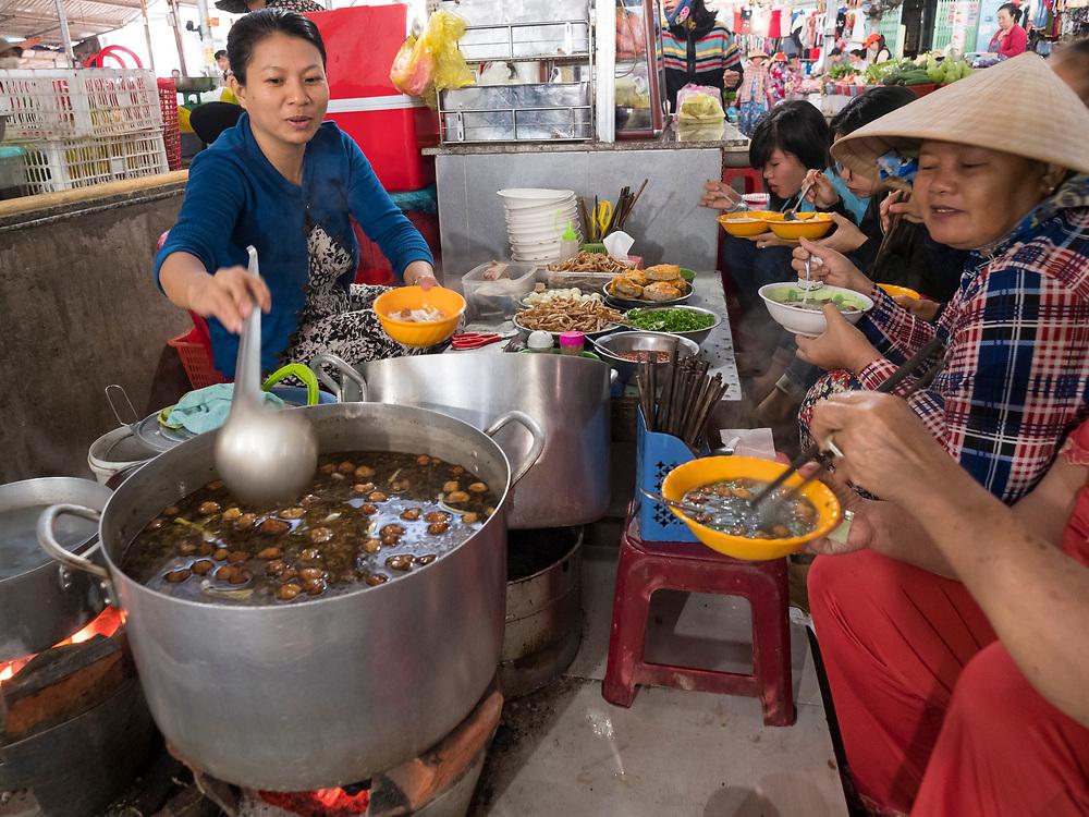 Asia, Vietnam, Mui Ne. Woman serving soup to customers in an indoor market.
