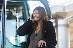 Young woman talking on mobile phone and standing in front of bus, Freiburg im Breisgau, Baden-Württemberg, Germany