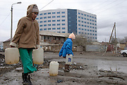 Atyrau, Kazakhstan, 14/11/2003..Residents in the centre of the old town collect water from a street pump with the new River Palace 5 star hotel amd office complex occupied by foreign oil companies behind.