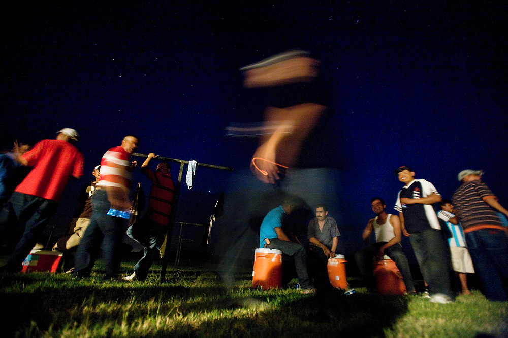 Migrant workers listen to music and fellowship in the backyard of their community housing during a party celebrating a huge harvest of peaches.