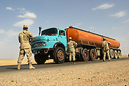 """ICDC soldiers man a roadblock (TCP in military lingo, or """"traffic control point"""") outside Qayarray, Iraq. They Iraqis learn the basics of running a roadblock at their training camp, and U.S. soldiers guide and protect them while they practice."""