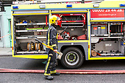 A London Fire Brigade fire officer collects an axe from the fire engine while responding to an emergency caused by an explosion in a small shop in North London, United Kingdom.