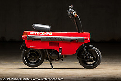 """Sam Hubbard's Honda Motocompo """"Trunk Bike"""" that was sold as an option to fit in the trunk of the Honda Today and Honda City cars between 1981-1983. To make it even more compact, the handlebars and seat fold into the plastic body. This compact bike is cealebrated today at bike meet-ups devoted to them. The Handbuilt Show. Austin, Texas USA. Friday, April 12, 2019. Photography ©2019 Michael Lichter."""