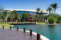 View across landscaped lake and park towards Microsoft office at Dubai Internet City in United Arab Emirates UAE